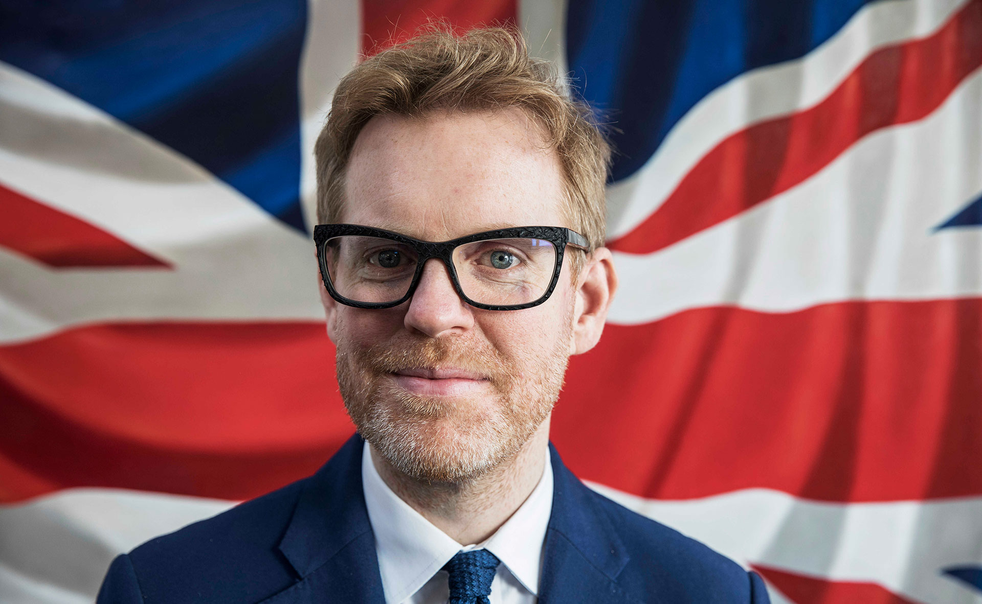 British eyewear designer Tom Davies in front of the Union Jack